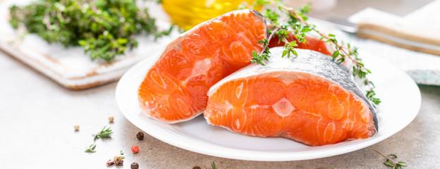 Fresh raw salmon fish steaks on white kitchen background. Banner © Sea Wave