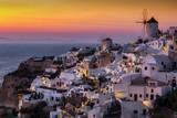 Blick auf das Dorf Oia mit seinen Windmühlen und weißen Häusern bei Sonnenuntergang, Kykladen, Griechenland