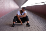 Portrait of a stylish African-American hipster guy sitting on a skateboard on a bridge sidewalk  - 249200613