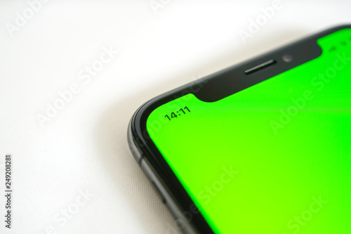 Side view detail of smartphone detail with chroma green screen and icons for the current hour, battery charge wi-fi and network lte signal - 249208281