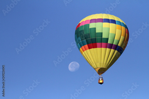 Hot air balloon in flight with moon in the background