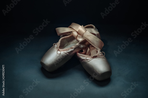 Pointe shoes ballet dance shoes with a bow of ribbons beautifully folded on a dark background. © andreyphoto63