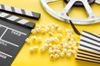 Leinwanddruck Bild - Cinema concept. Clapperboard, film stock and popcorn on yellow background