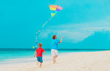 father and little son flying kite on beach
