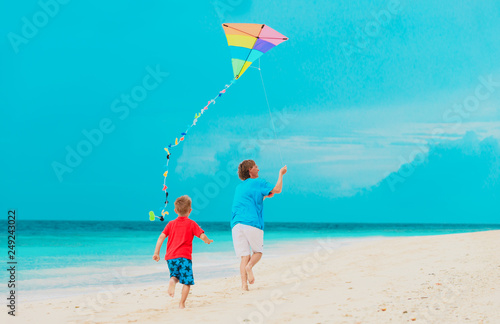 Foto Murales father and little son flying kite on beach
