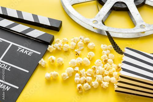 Leinwanddruck Bild Cinema concept. Clapperboard, film stock and popcorn on yellow background