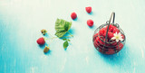 Fresh raspberry in tiny metal vintage basket on blue shabby wooden background top view.