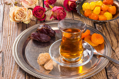 various dried fruits and  Turkish tea in Armudu glass on wooden table. © phant