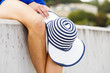 Unrecognizable woman holding summer sun hat in white and blue colors showing her slim legs. Female equipped with vacations essentials.