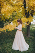 A beautiful bride in a beige dress is standing in a park with yellow leaves. The princess with a crown enjoys the fall. Wedding portrait of a cute bride with brown hair.