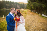Beautiful wedding couple posing outdoor at countryside