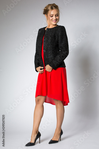Beautiful woman posing in red dress and black sweater