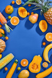 Collection of fresh yellow fruit and vegetables on the blue background