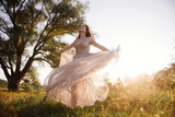Wedding near the river in field at sunset with brown horse. Bride in light airy dress in color of dusty rose. Beige dress with sparkles. Light suit with bow tie. bride and groom embrace and kiss.