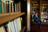 Groom photographed in his private library. Luxury Wedding