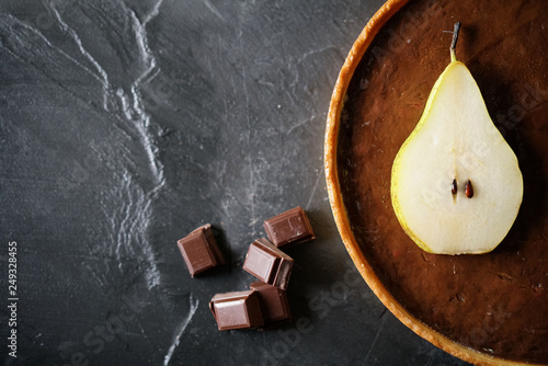 Top view of delicous chocolate pear tart on slate with text space