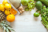 Flat lay composition with measuring tape, healthy vegetables and fruit on wooden background. Weight loss diet