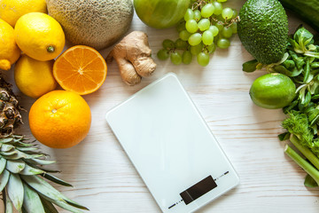Flat lay composition with kitchen scales, healthy vegetables and fruit on wooden background. Weight loss diet