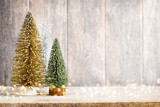 Artificial Christmas tree on a wooden background. - 249364481