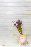 dried lavender and dried poppy in an iron watering can on a light wooden background. style -