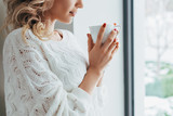 Cropped view of woman in knitted sweater drinking coffee - 249373214