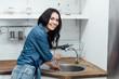 Laughing brunette girl in denim shirt using plunger in kitchen