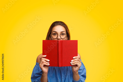 Woman in glasses holding book near face
