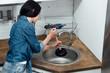 Brunette woman in denim shirt using plunger in kitchen