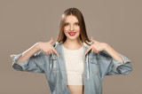 Female teenager laughs, pointing to the empty space. Sopycpase. Bright make-up and fashion beautiful appearance - 249387660