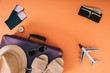 Leinwanddruck Bild - top view of summer accessories on travel bag, plane model, wallet and passports with tickets on orange background