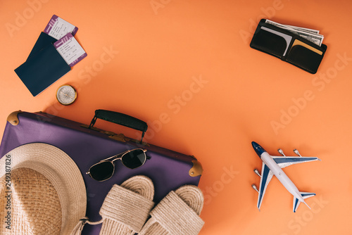 Leinwanddruck Bild top view of summer accessories on travel bag, plane model, wallet and passports with tickets on orange background
