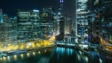 Beautiful time lapse of the many high-rise buildings along the Chicago River at night.