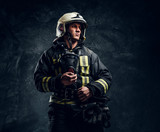 Studio portrait in a dark studio against a textured wall. Brutal firefighter in uniform and safety helmet holding an oxygen mask and looking sideways with a confident look. - 249404813