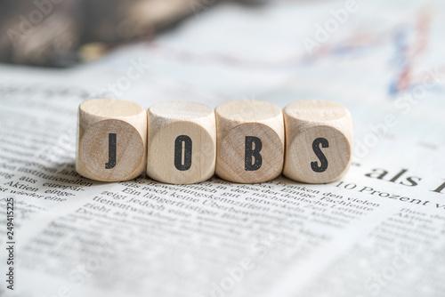 Leinwanddruck Bild Würfel mit Aufschrift JOBS auf einer Tageszeitung