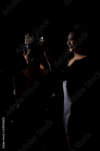Two Silhouette Shadow Back Rim Light of Miss Pageant Beauty Queen Contest put Silver Diamond Crown on Winner final moment most beautiful woman in world universe, studio lighting dark black background