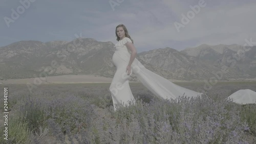 Pregnant Woman in White Flowing Dress in Lavender Field