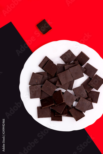 White plate with chocolate on a colored background © i_valentin
