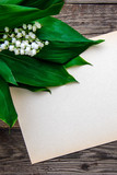 Bouquet of lilies of the valley and a sheet of paper on a wooden background