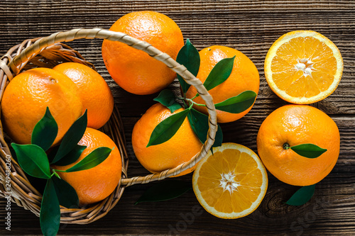 Fresh oranges in a basket on wooden table. Orange fruit, top view.
