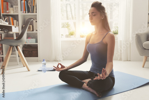 Young woman practicing meditation at home - 249494874