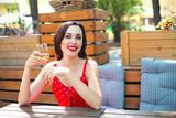 Woman wearing polka dots dress having wine in a restaurant - 249496053