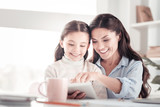 Helpful understanding mother teaching her funny energetic daughter reading - 249497205