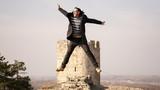 A man in a coat jumping in the air at Kalamegdan fortress in Belgrade - 249497290