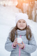 Portrait of cute little kid girl playing with snowballs outdoors
