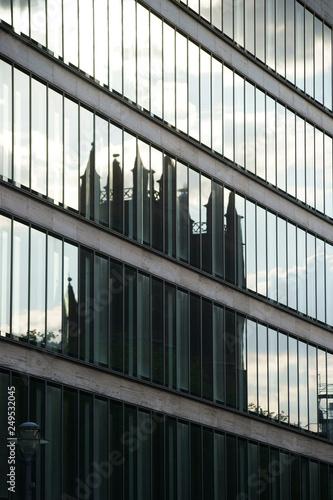 Ein altes Gebäude mit kleinen Türmen spiegelt sich in der modernen Fassade eines Hochhauses. . © ginton
