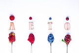Top view of berries mixed (strawberries, raspberries, blueberries and blackberries) on metal spoons on white background. Food concept. Flat lay. Nature concept. A place for your inscription.