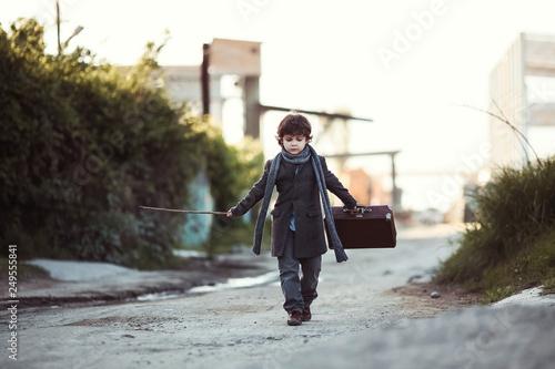 eeade578a0 A little boy in a coat goes. Little traveler. Tourism. Vintage. Escape