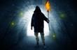 Leinwanddruck Bild - Ugly man with burning flambeau walking in a dark tunnel