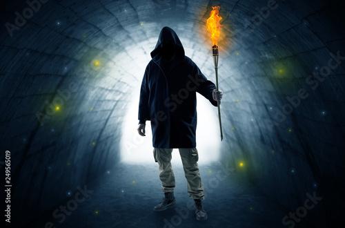 Leinwanddruck Bild Ugly man with burning flambeau walking in a dark tunnel