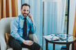 Waist up of cheerful businessman talking on the phone in hotel room